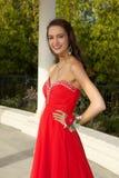 Lycklig tonårs- flicka som går till studentbalen i en röd klänning royaltyfria foton