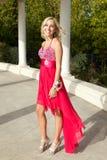 Lycklig tonårs- flicka som går till studentbalen i en röd klänning Fotografering för Bildbyråer
