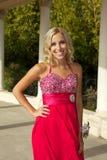 Lycklig tonårs- flicka som går till studentbalen i en röd klänning Royaltyfri Foto