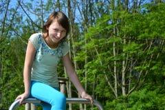 Lycklig tonårs- flicka som ler sammanträde på ett metallrör i parkera Royaltyfri Bild