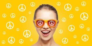Lycklig tonårs- hippy flicka i skuggor med fredtecknet Arkivbild