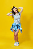 Lycklig tonårs- kvinna över gul bakgrund royaltyfri foto