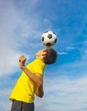 Lycklig tonårs- pojke med en fotbollboll på hans huvud på bac för blå himmel arkivbild