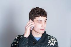 Lycklig tonårs- pojke som talar på hans mobiltelefon Arkivfoto