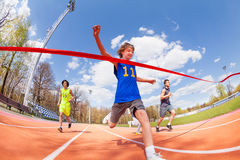 Lycklig tonårs- sprinter som först kommer till mållinjen royaltyfri foto