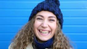 Lycklig tonåringflicka med galna skratt för lockigt hår som lutar mot den blåa väggen lager videofilmer