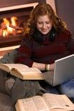 Lycklig tonårs- flicka som hemma lär med böcker Arkivbild