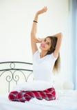 Lycklig tonårs- flicka som vaknar upp och inomhus ler Arkivfoton