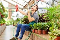 Lycklig trädgårdsmästare som sjunger i växthus Arkivbild
