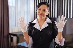 Lycklig trevlig hotellhembiträde som visar hennes händer i disponibla handskar Royaltyfria Foton