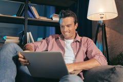 Lycklig trevlig man som ser bärbar datorskärmen royaltyfria bilder