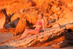 Lycklig tropisk strandsolnedgång för ung kvinna Arkivbild