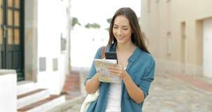 Lycklig turist- bläddra mobiltelefon i gatan