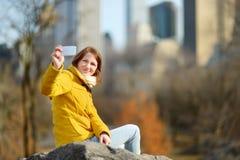 Lycklig turist för ung kvinna som tar bilder på Central Park i New York City Kvinnlig handelsresande som tycker om sikter av i st royaltyfri fotografi