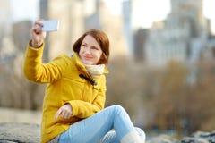 Lycklig turist för ung kvinna som tar bilder på Central Park i New York City Kvinnlig handelsresande som tycker om sikter av i st royaltyfria foton