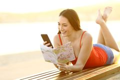 Lycklig turist- kontrollerande telefon och handbok på stranden royaltyfria foton