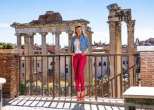 Lycklig turist- kvinna framme av Roman Forum som åt sidan ser royaltyfria bilder