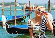 Lycklig turist och gondoler i Venedig, Italien gladlynt blondin Arkivfoto