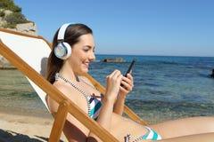 Lycklig turist som lyssnar till musik på stranden på ferie royaltyfri foto