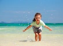 Lycklig tyckande om ungeflicka som spelar och plaskar med vatten på blått Arkivfoto
