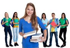 Lycklig tysk kvinnlig student med böcker och gruppen av studenter arkivfoton
