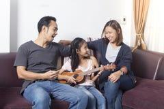 Lycklig ukulele för lek för familjundervisningdotter royaltyfria bilder