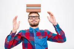 Lycklig underhållande man i exponeringsglas med böcker på hans huvud Royaltyfri Bild