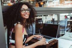 Lycklig ung affärskvinna i exponeringsglas i ett utomhus- kafé med hennes netbook och en kopp kaffe; en gladlynt lockig caucasian royaltyfri fotografi