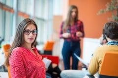 Lycklig ung affärskvinna med hennes personal, folkgrupp i bakgrund på det moderna ljusa kontoret inomhus Royaltyfria Bilder