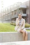 Lycklig ung affärskvinna som använder mobiltelefonen, medan sitta på väggen mot kontorsbyggnad Royaltyfria Foton
