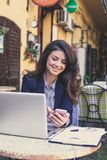 Lycklig ung affärskvinna som arbetar på kafét, genom att använda mobiltelefonen royaltyfri fotografi