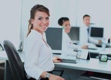 Lycklig ung affärskvinna som ser behind, och hennes kollegor som arbetar på kontoret Arkivbild