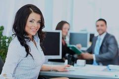 Lycklig ung affärskvinna som ser behind, och hennes kollegor som arbetar på kontoret Royaltyfria Foton