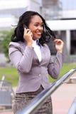 Lycklig ung affärskvinna som talar på mobiltelefonen Arkivfoton