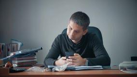 Lycklig ung affärsman som i regeringsställning sitter med affärslegitimationshandlingar på tabellen Stiligt manarbete som skriver lager videofilmer