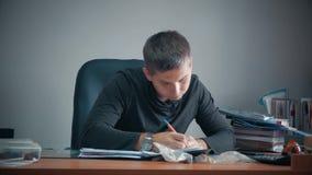 Lycklig ung affärsman som i regeringsställning sitter med affärslegitimationshandlingar på tabellen Stiligt manarbete som skriver arkivfilmer