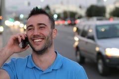 Lycklig ung affärsman som kallar med mobiltelefonen Han kallar något vid mobiltelefonen på gatan Royaltyfri Bild