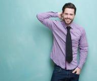 Lycklig ung affärsman som ler mot blå bakgrund royaltyfri fotografi