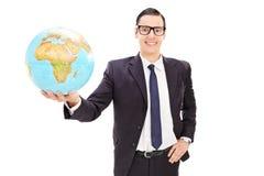 Lycklig ung affärsman som rymmer ett jordklot Arkivbilder
