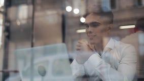 Lycklig ung affärsman som sitter på en tabell i ett kaféarbete på en bärbar dator Frilans kommunikation, IT som är lyckad arkivfilmer