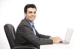 Lycklig ung affärsman som arbetar på bärbara datorn Royaltyfri Bild