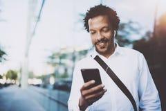 Lycklig ung afrikansk amerikanman i headphone som går på den soliga staden och tycker om för att lyssna till musik på hans elektr Royaltyfria Bilder