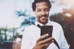 Lycklig ung afrikansk amerikanman i headphone som kontrollerar emailasken på den soliga staden och tycker om för att lyssna till  Royaltyfri Fotografi
