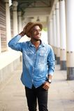 Lycklig ung afrikansk amerikanman som går med hatten Royaltyfri Foto