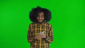 Lycklig ung afrikansk amerikanman som rymmer pengar i hans händer och ser kameran på grön skärm- eller chromatangent stock video