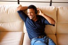 Lycklig ung afrikansk amerikanman som ser bort och ler med head telefoner Arkivbild