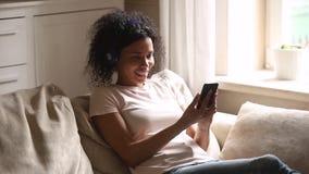 Lycklig ung afrikansk kvinna som bär trådlös hörlurar genom att använda smartphonen arkivfilmer
