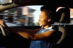 Lycklig ung afrikansk kvinna som kör en bil fotografering för bildbyråer