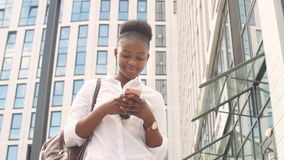 Lycklig ung afrikansk kvinnlig student i den vita grundläggande skjortan med läderryggsäcken som ser hennes smartphone lager videofilmer