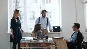 Lycklig ung aktiv le manlig utövande chef som pratar med kollegor under avbrott i modernt ljust vindkontor arkivfilmer